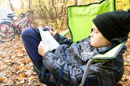 child reading in a campchair