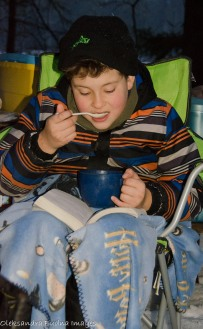 kid eating in a camping chair