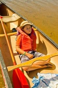 kid sleeping in a canoe