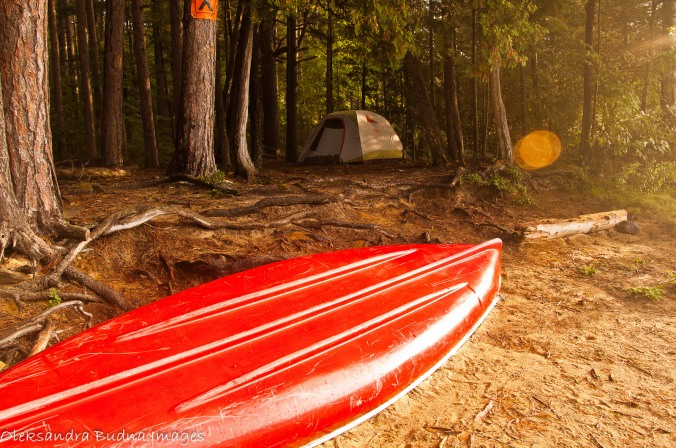 early morning at a campsite - tent and red canoe