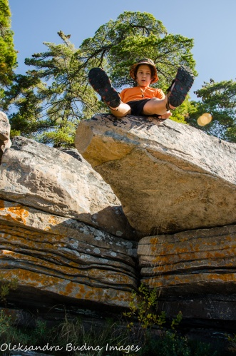 kid sitting on a rocky ledge at Killbear Provincial Park