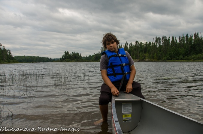 child sitting on the bow of a canoe