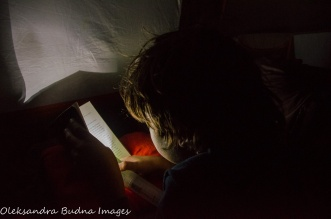 reading in a tent with a flashlight