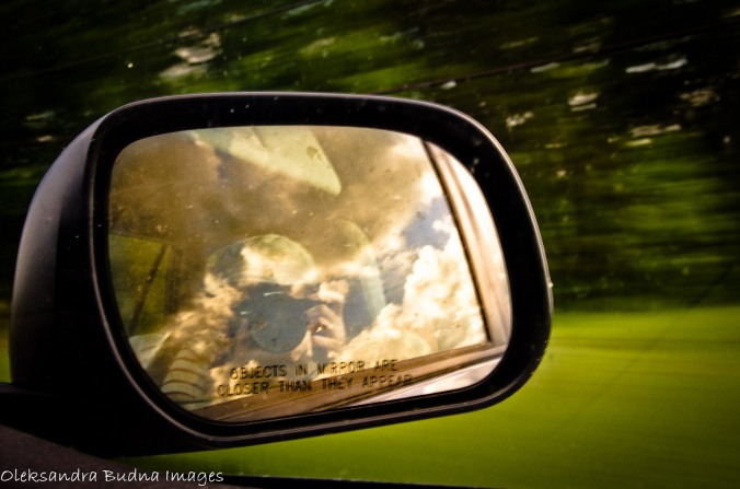 clouds and camera reflected in the side-view mirror of the moving car