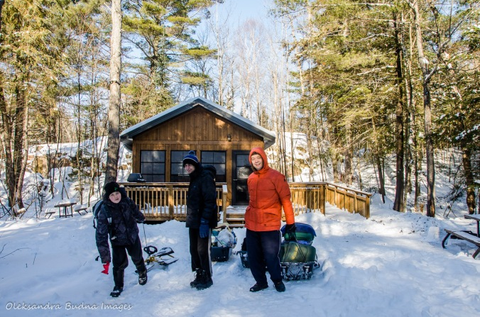 pulling gear in sleds in front of a cabin in Killarney