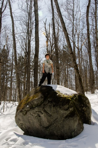 kid on a rock in the forest in the winter
