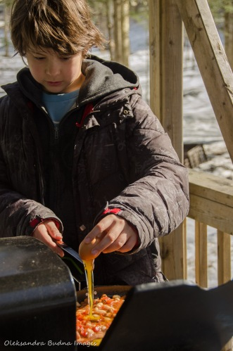 child cooking outside at Silet Lake