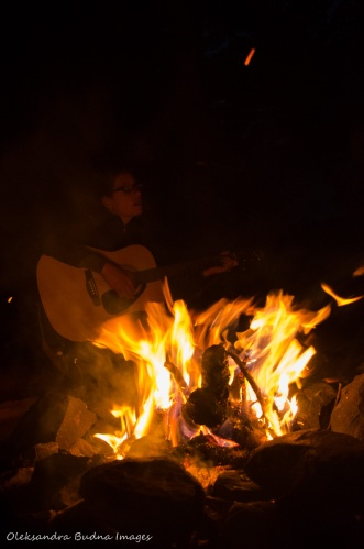 playing the guitar around the campfire