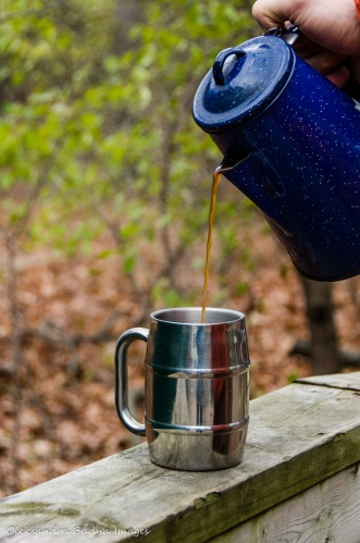 pouring coffee into a mug at a campsite