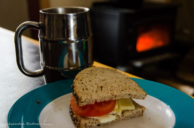 sandwish and a cup of coffee in front of a wood stove in a four-season tent in Gatineau