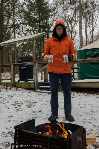 holding two cups of coffee near the campfire yurt 477 in Pinery