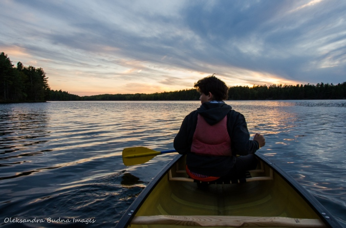canoeing against the sunset on Big Salmon Lake in Frontenac