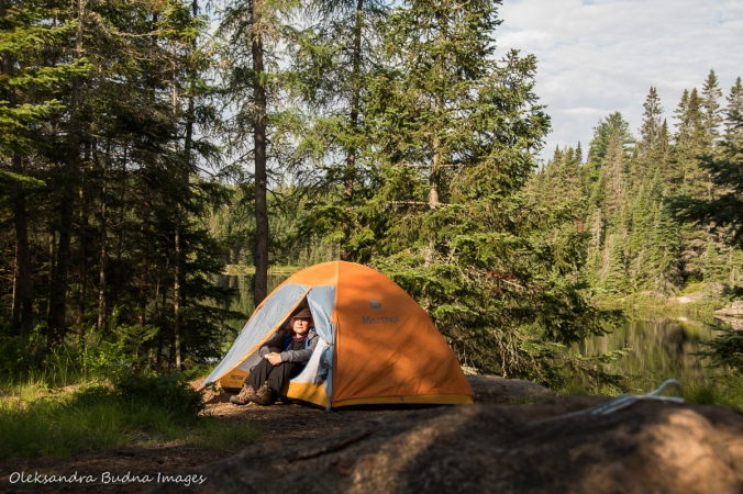 woman sitting by the tent on Faya Lake site in Algonquin