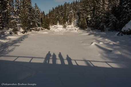 shadows of people on the bridge on the snow covered lake