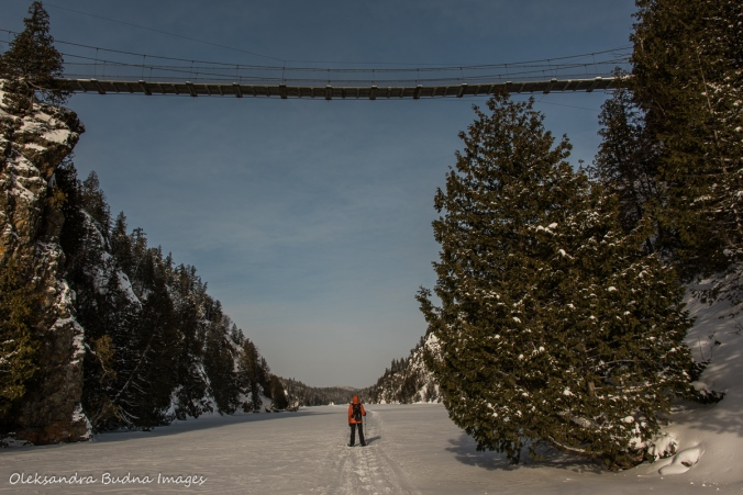 snowshoeing under suspension bridge on Lac La Haie in Parc National d'Aiguebelle