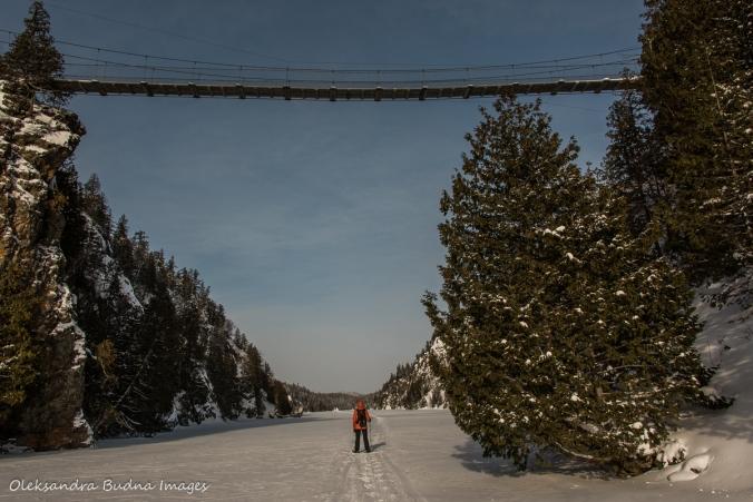 snowshoeing under suspension bridge on Lac La Haie in Parc National d'Aiguebelle