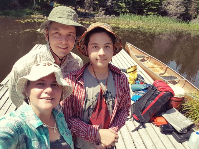 family selfie on the dock at Widgawa Lodge with a canoe and camping gear in the background