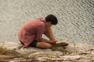 reading by the water at campsite 179 on Grace Lake in Killarney
