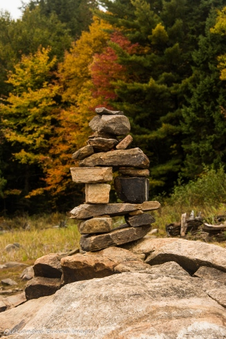 rock sculpture against fall foliage
