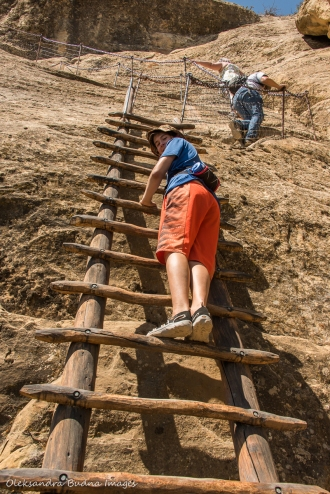climbing a ladder at Balcony House in Mesa Verde