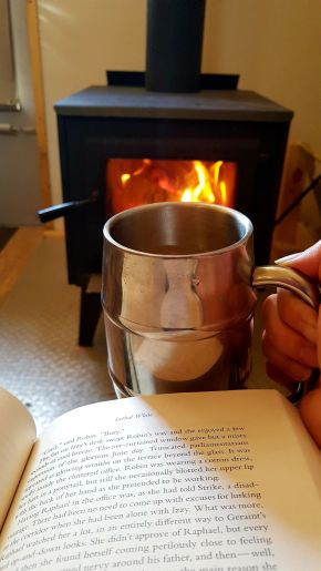 book, cup of coffee, wood stove inside oTENTik in Point Pelee