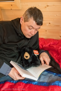 reading on a bed inside Black Bear's Den cabin at Silent Lake Provincial Park