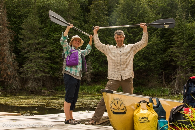holding paddles up celebrating the end of a canoe trip