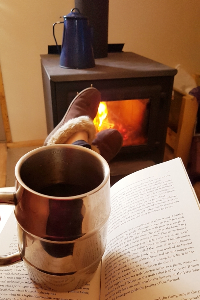 coffee and book in front of a wood stove