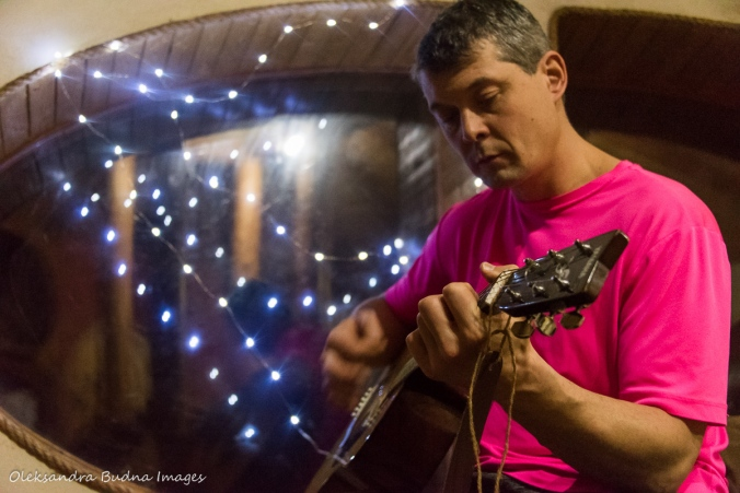 playing the guitar in the Hobbit House at Les Toits du Monde