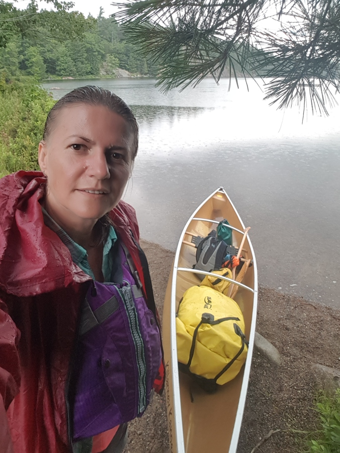 standing by the canoe at a put-in on Johnnie Lake in Killarney