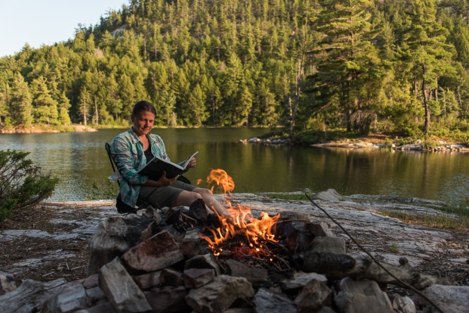 reading by the campfire on site 179 on Grace Lake in Killarney