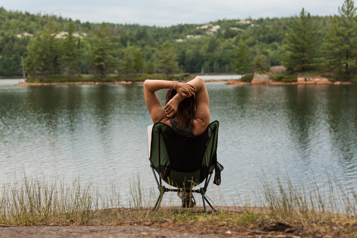 sitting in a camping chair by Ruth-Roy Lake in Killarney