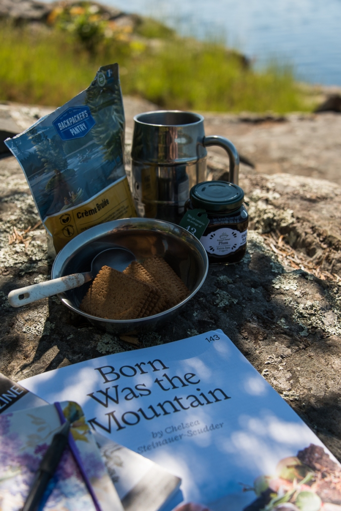 cup of coffee, creme brulee from Backpacker's Pantry, jam and cookie, magazine by the lake
