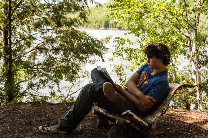 reading in a hand-made chair on a campsite on Manitou Lake in Algonquin