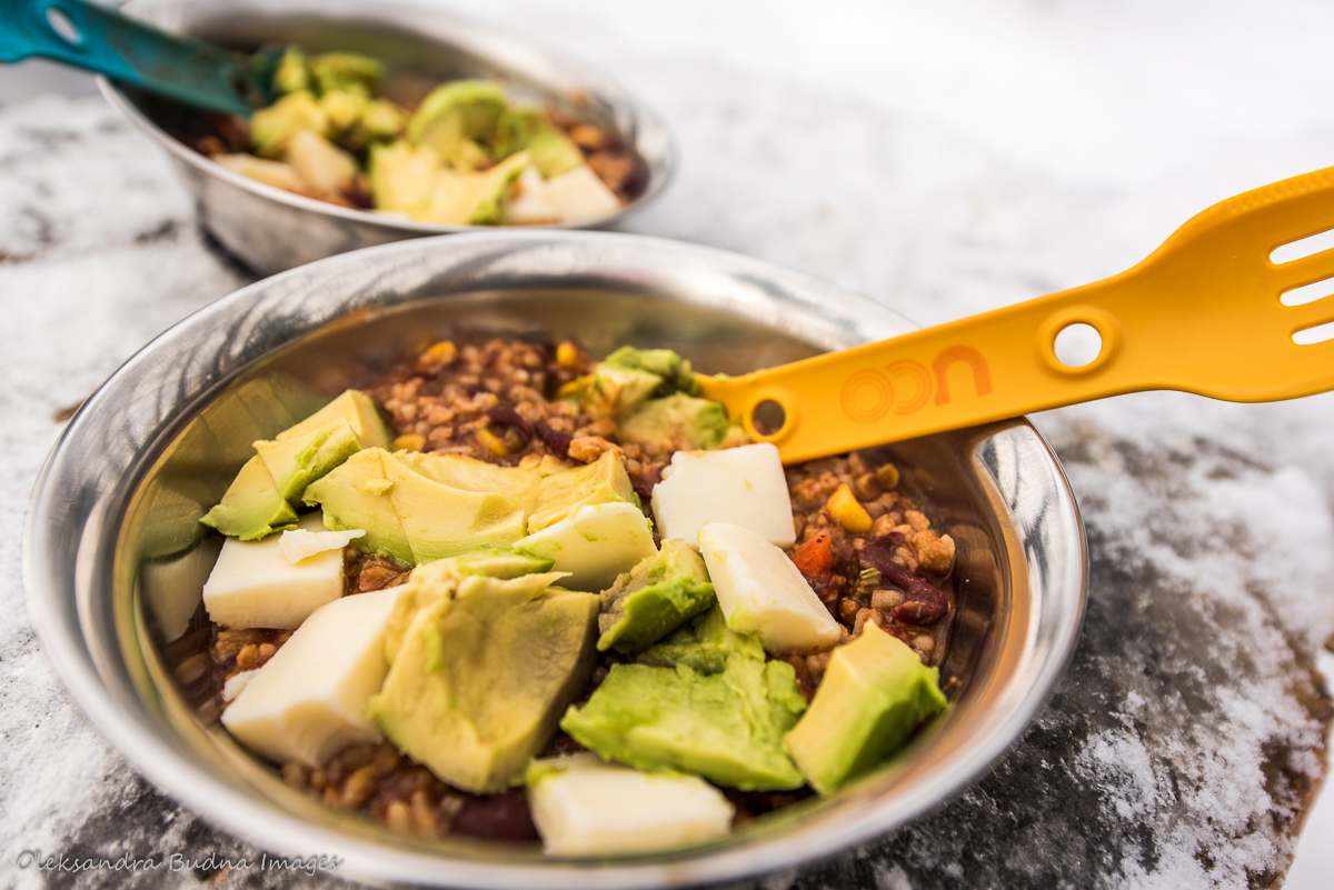 Chili with avocado and cheese in a camping bowl