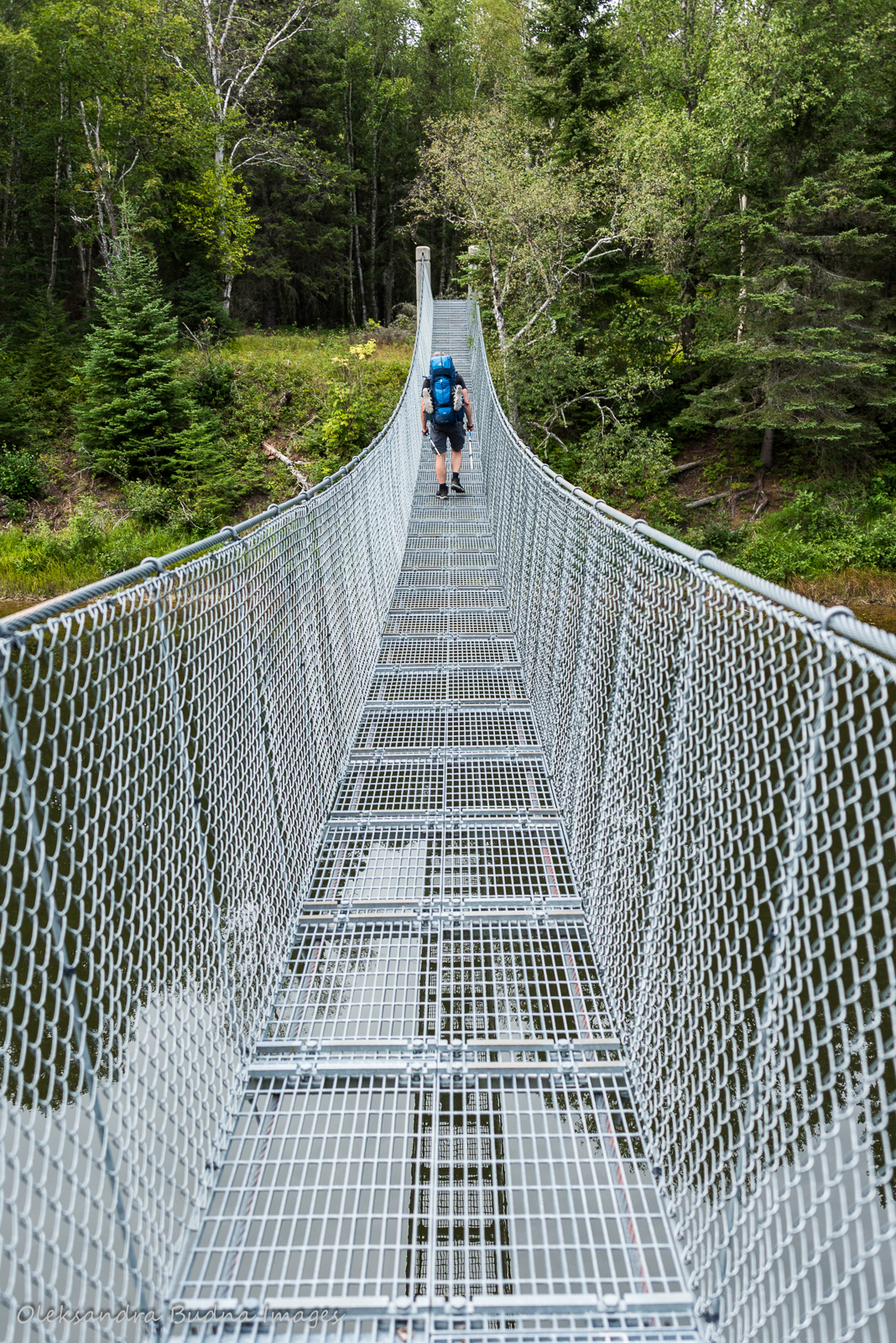 Crossing suspension bridge over Willow River while backpacking in Pukaskwa